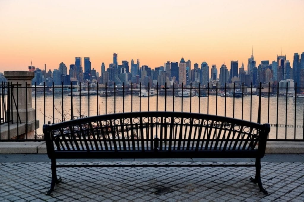Bench in park and New York City midtown Manhattan at sunset with skyline panorama view over Hudson River